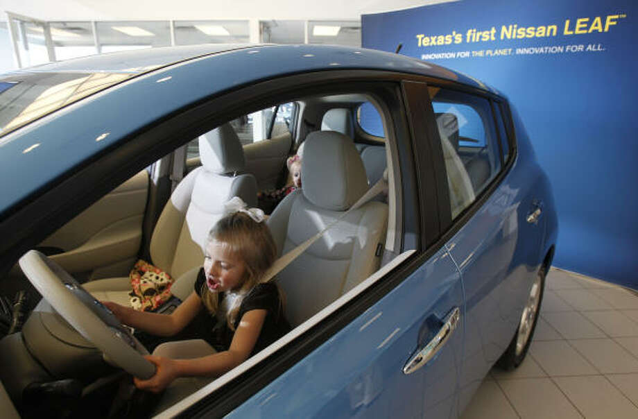 Five-year-old Allie Sauers is ready to roll in her family's new Nissan Leaf, with her seat belt buckled. Her sister Amie, 2, is along for the ride Tuesday at Clear Lake Nissan. Her sister Annabel is there, too, hidden in the back seat. Photo: Melissa Phillip :, Chronicle