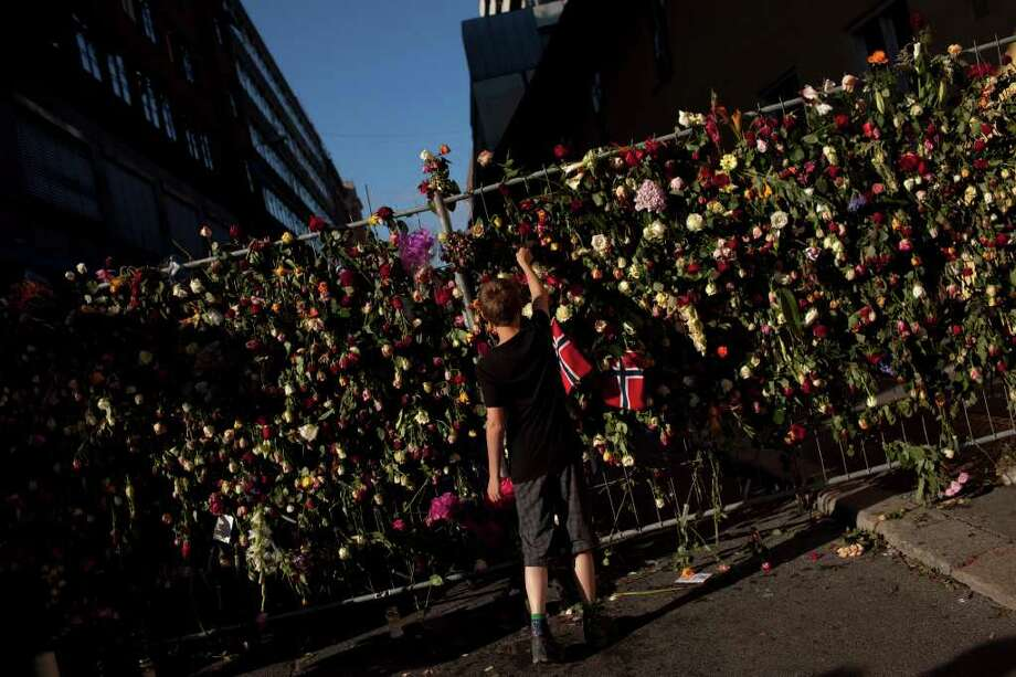 A boy places a rose on a fence surrounding the area where eight people were killed in Friday's blast in Oslo Wednesday, July 27, 2011.  (AP Photo/Emilio Morenatti) Photo: Emilio Morenatti / AP