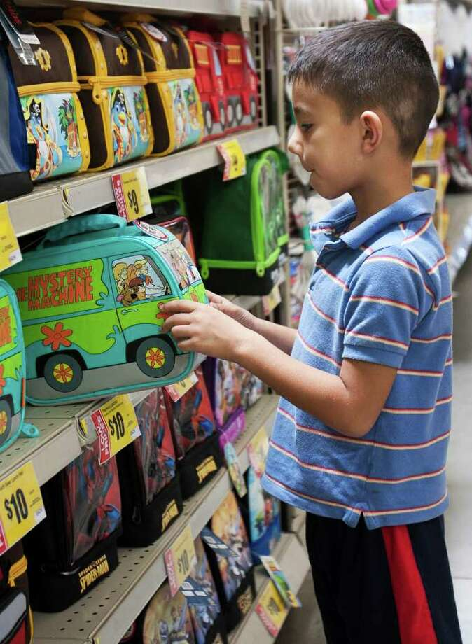 Johnny Garcia, 6, looks at a Scooby Doo lunchbox Tuesday, July 26, 2011, at the H.E.B Plus on New Braunfels Ave. Johnny's father, John Garcia was pricing items his kids  will need for school before deciding where to buy them. Parents are expected to spend more cautiously on back-to-school shopping trips this year according to National Retail Federation survey data. Photo: SALLY FINNERAN, SALLY FINNERAN/sfinneran@express-news.net / sfinneran@express-news