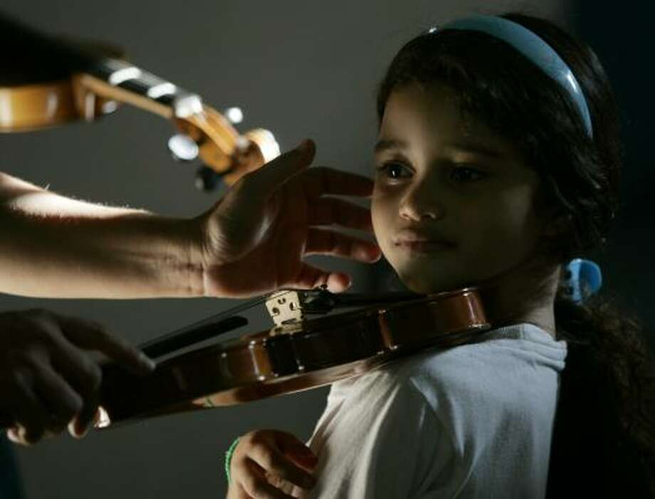 Laura Balda learns how to hold the violin at the Youth and Children's Symphonic Orchestras of Venezuela system school in San Sebastian de los Reyes, Venezuela. Photo: FERNANDO LLANO, ASSOCIATED PRESS