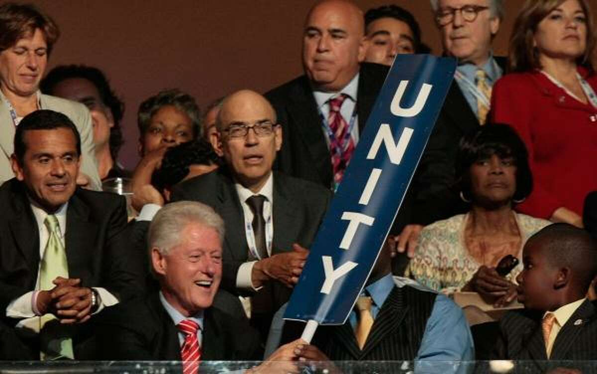 """Former President Bill Clinton holds a """"Unity"""" sign as he sits in the audience at the Democratic convention Tuesday night."""
