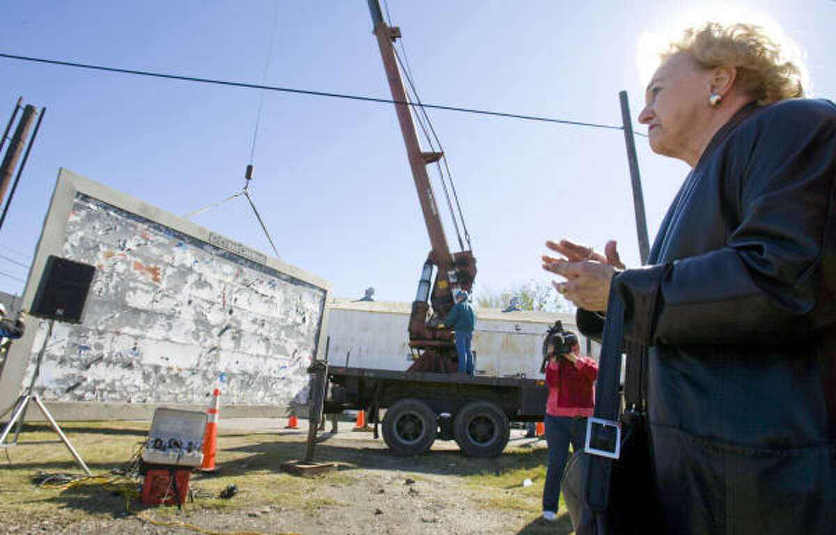 Eleanor Tinsley applauded on Jan. 13 as a billboard was removed at the intersection of Polk and Roberts Streets in Houston.