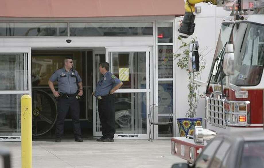 Security guards stand at an entrance of Houston Community College West Loop Center on Monday after a carbon monoxide call drew emergency personnel to the scene. Construction workers, who were laying a concrete floor in the second level, complained of headaches. Photo: Julio Cortez, Chronicle
