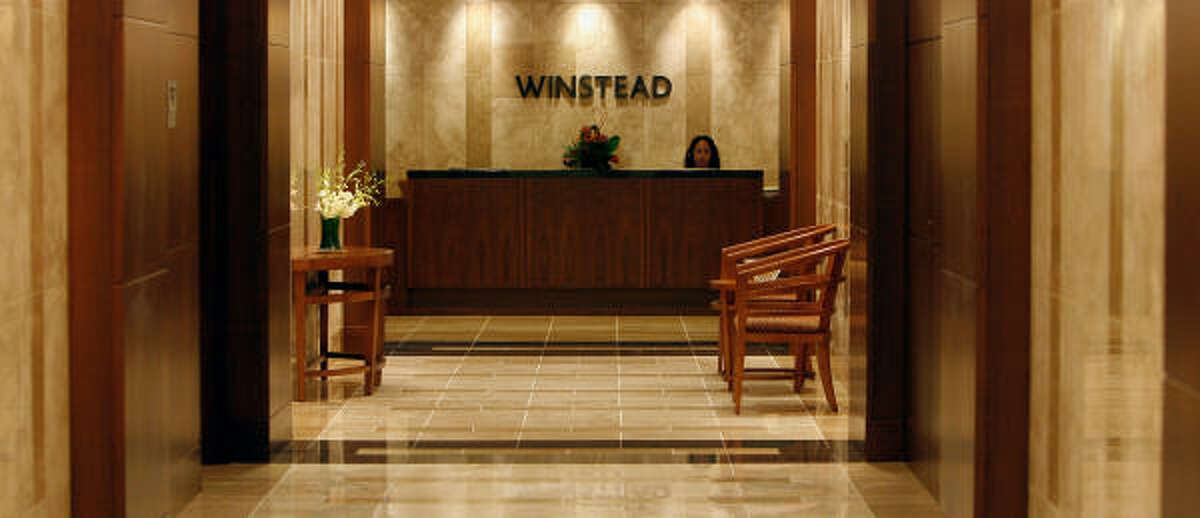 Receptionist Monica Dixon sits at the desk under the Winstead sign at the Winstead PC law offices.