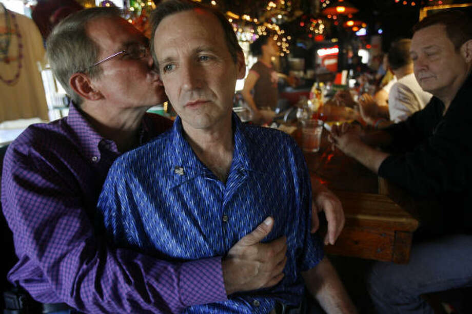 "Victor Clements embraces partner Marc Bosaw, who was attacked on Saturday on Rosenberg Avenue in Galveston. ""I almost lost my soul mate,"" Clements says. Three men have been charged. Photo: Mayra Beltran, Chronicle"