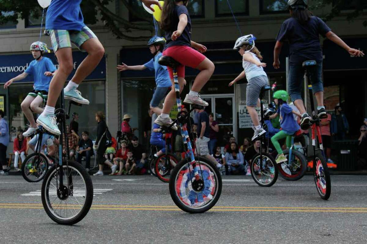 Young unicyclists perform at the Greenwood Seafair parade along Greenwood Avenue in Seattle on Wednesday, July 27, 2011.