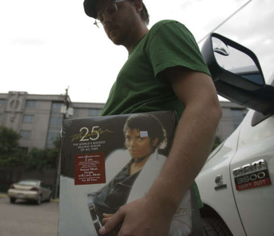 Derek Schumate holds on to a Michael Jackson 25th Anniversary album purchased from Soundwaves on Montrose in Houston on Thursday. Photo: Billy Smith II, Chronicle