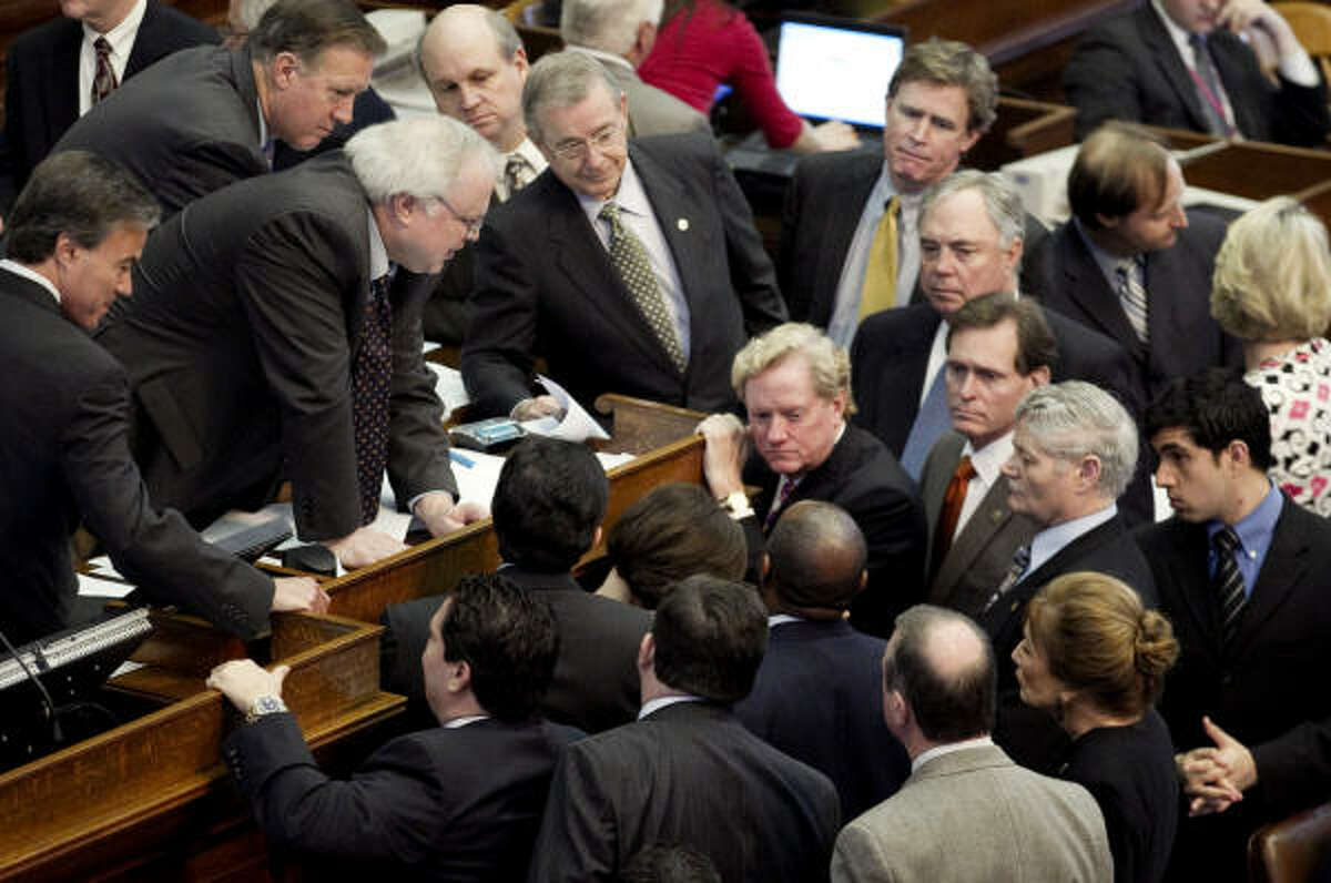Texas state representatives gather around House Parliamentarian Chris Griesel, at left leaning over the dais, during debate of the budget bill on Sunday.