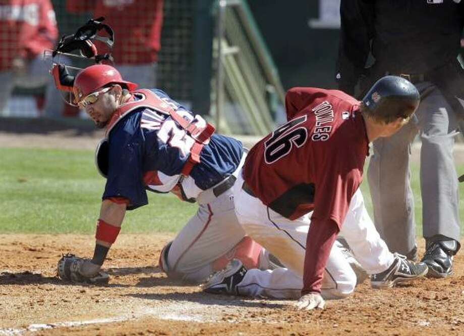 Astros catcher J.R. Towles slides safely into home in front of Washington Nationals catcher Wil Nieves. Photo: Rob Carr, AP