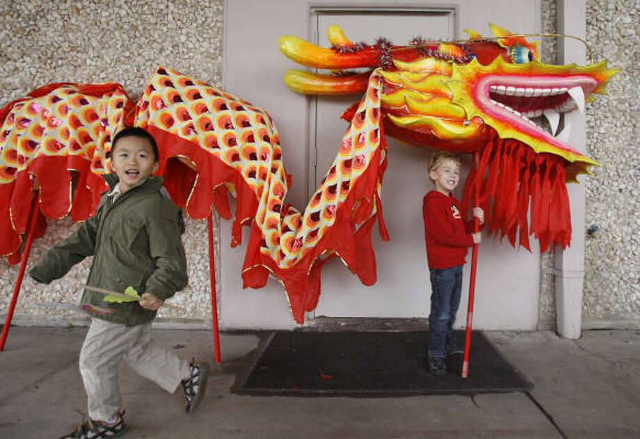 Andy Cai, 6, of Sugar Land, and Kjell Aspelin, 5, of Santa Fe, pose for photos taken by their parents Saturday during a celebration to welcome the Chinese New Year at the Chinese Community Center. Photo: Julio Cortez, Chronicle