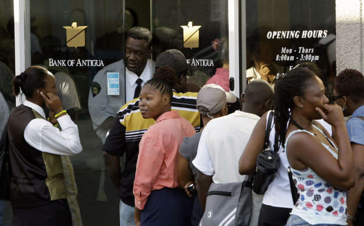 A guard speaks with Bank of Antigua customers lined up outside the St. John's branch Wednesday. Antigua's Prime Minister Baldwin Spencer urged people not to panic over a U.S. fraud probe involving R. Allen Stanford.