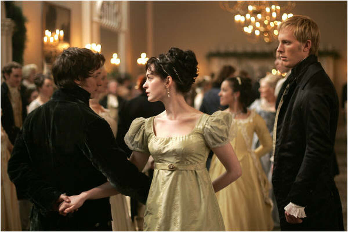In Becoming Jane, James McAvoy (left) is Tom Lefroy and Anne Hathaway (center) is Jane Austen. Laurence Fox (right) plays Mr. Wisley.