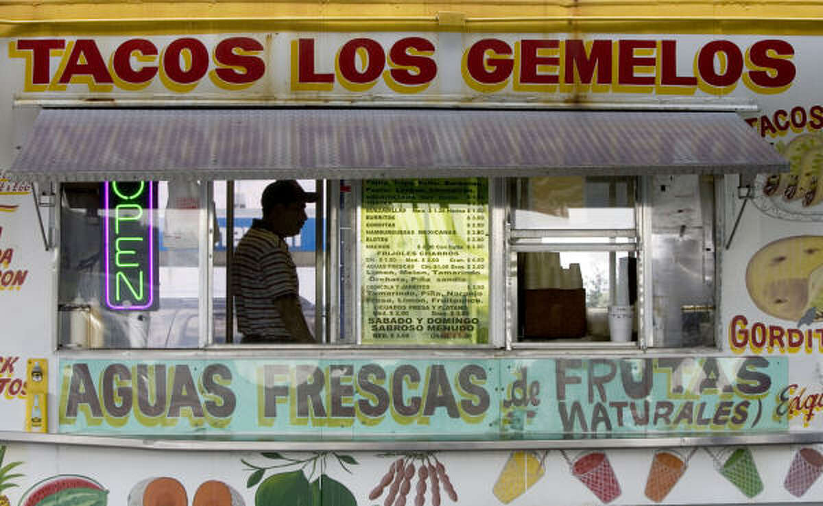 Socorro Tapia walks past the window of his taco wagon. Tapia and other Hispanic taqueria operators are fighting regulations that require wagons to undergo daily inspections and vendors to display permission from property owners to park.