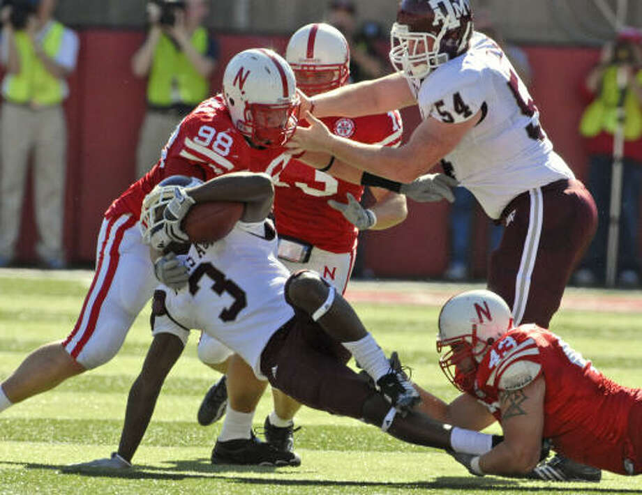 Texas A&M's Mike Goodson (3) is tackled by Nebraska's Zach Potter (98) and Ty Steinkuhler (43). Photo: Dave Weaver, AP