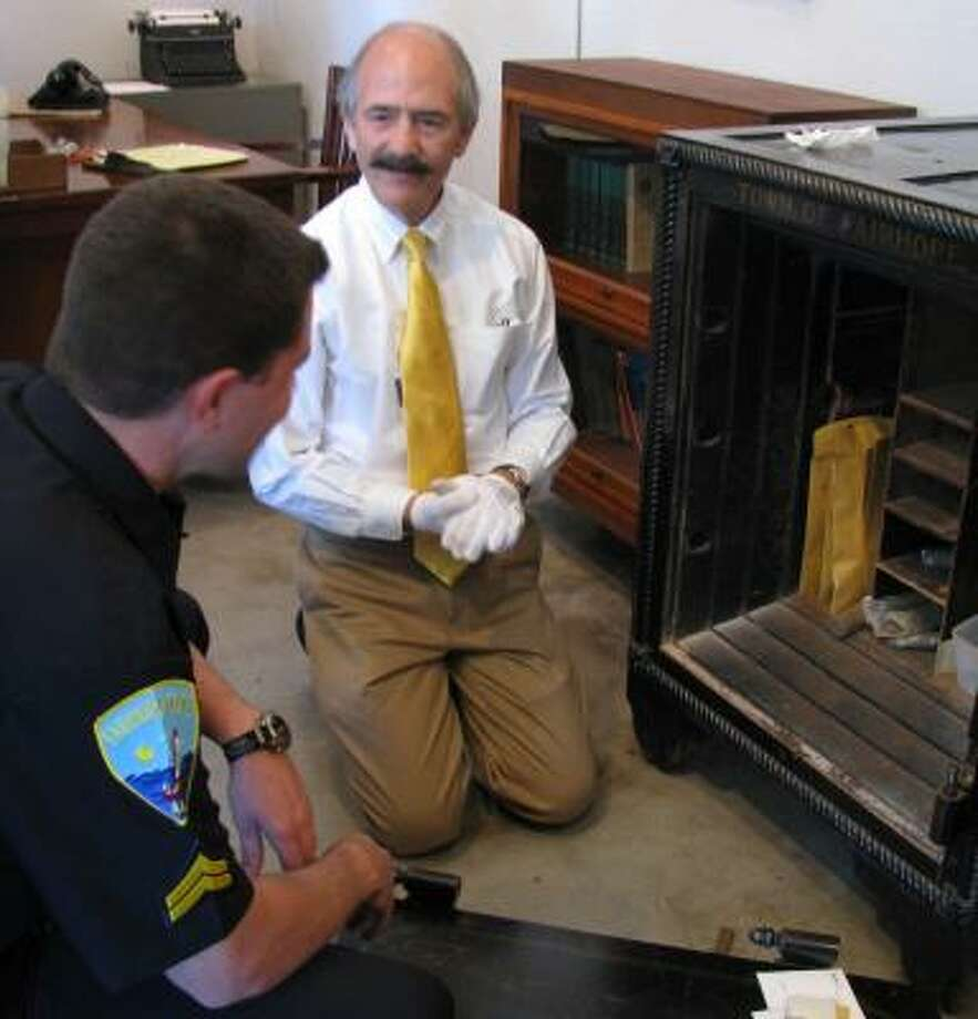 Donnie Barrett, director of the Fairhope Museum of History, shows police Cpl. Brett Murray a 37-year-old stash in the city's safe. Photo: RUSS HENDERSON, NEWHOUSE NEWS SERVICE