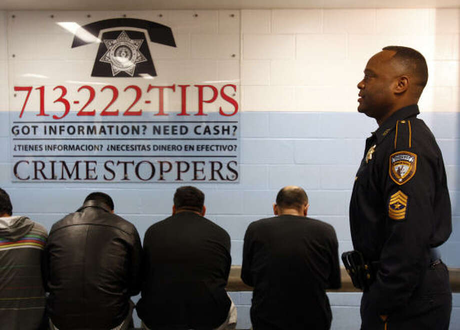 Sgt. Ronnie Holmes works at the Inmate Processing Center, where Crime Stoppers information graces the walls. The tips program initiated by Sheriff Adrian Garcia will have six monitors that flash Crime Stoppers data continuously in English and Spanish. Photo: Melissa Phillip, Houston Chronicle