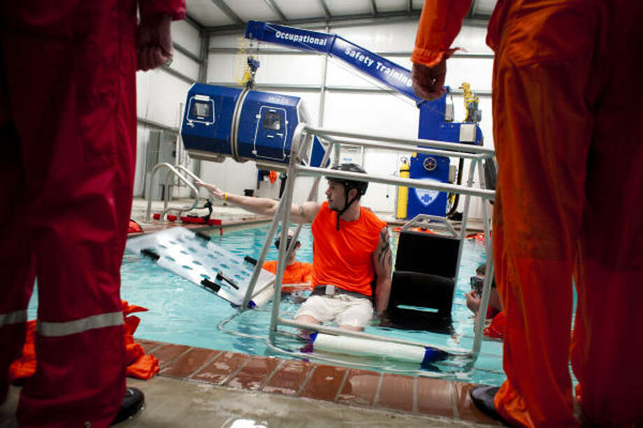 Survival instructor Garrett Hindt, buckled into a training chair, tells students how to escape from a sinking helicopter during a water survival class at Occupational Safety Training's building in Brookshire, just west of Katy. Photo: Eric Kayne :, For The Chronicle