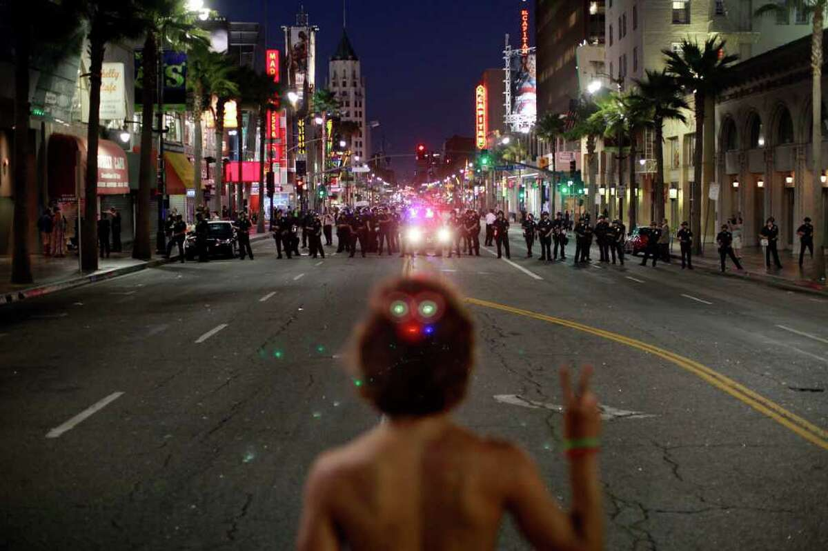 Noel Buller, 21, from Los Angeles, stands in the middle of Hollywood Boulevard in Los Angeles holding up a peace sign while facing a line of Los Angeles Police Wednesday. Police say a crowd became unruly outside the premiere of a documentary about the Electric Daisy Carnival rave. (AP Photo/Jay L. Clendenin/Los Angeles Times)