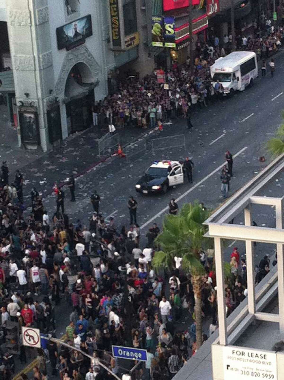 Police hold back a crowd outside Grauman's Chinese Theater in the Hollywood section of Los Angeles on Wednesday after a crowd became unruly outside the Hollywood film premiere of a documentary about the Electric Daisy Carnival rave, throwing bottles and vandalizing cars and refusing orders to disperse after they were forced to leave an overcrowded theater, authorities said.