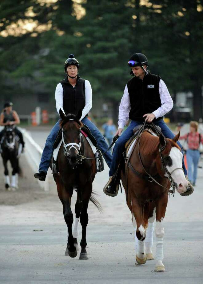 Uncle Mo, with exercise rider Patty Krotenko, left, and assistant trainer Mike McCarthy, heads to a speed workout just after dawn Thursday at Saratoga Race Course in Saratoga Springs. (Skip Dickstein / Times Union) Photo: SKIP DICKSTEIN