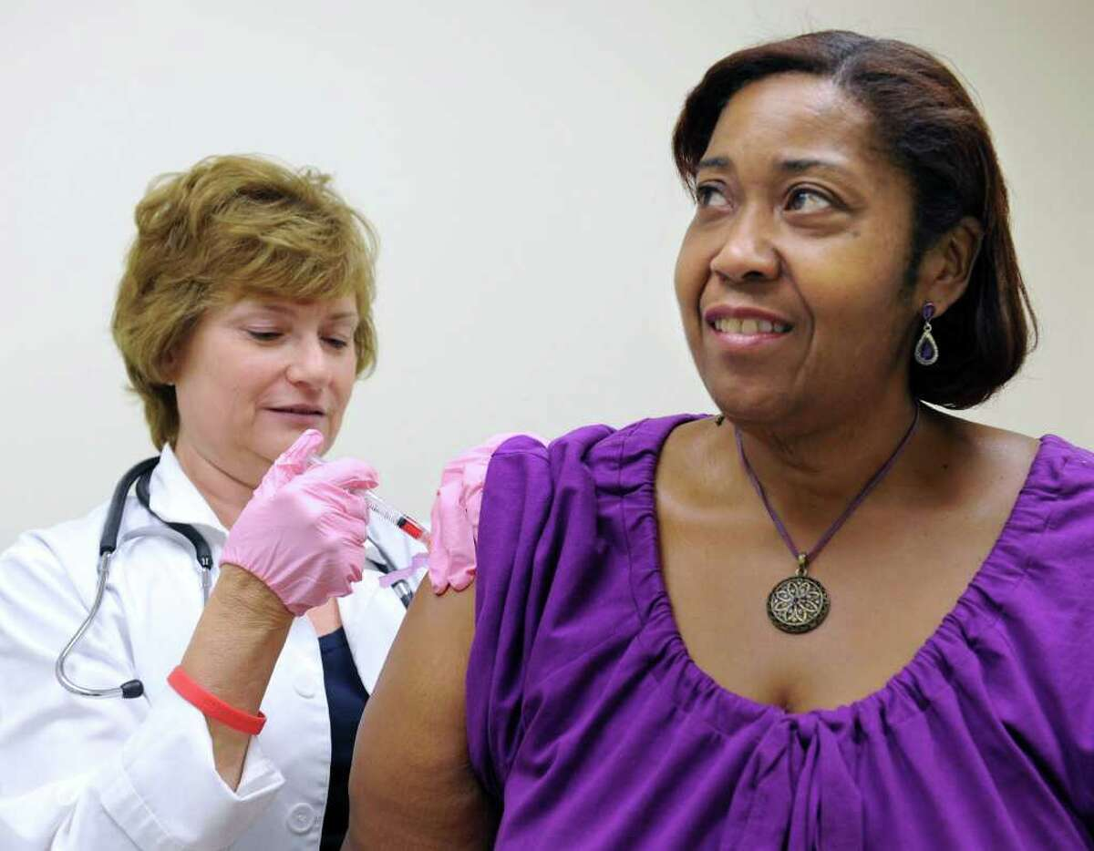 Judy Hottle, RN, left, assistant director of the Americares Clinic in Danbury, gives a shot to Dawn Coles, 51, of Danbury Wednesday. Photo taken Wednesday, July 27, 2011.
