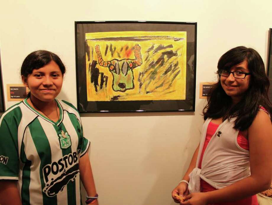 Iris Velez, left, and Damaris Llemas admire Irisí painting of ìThe Rising Bull.î Photo: Contributed Photo