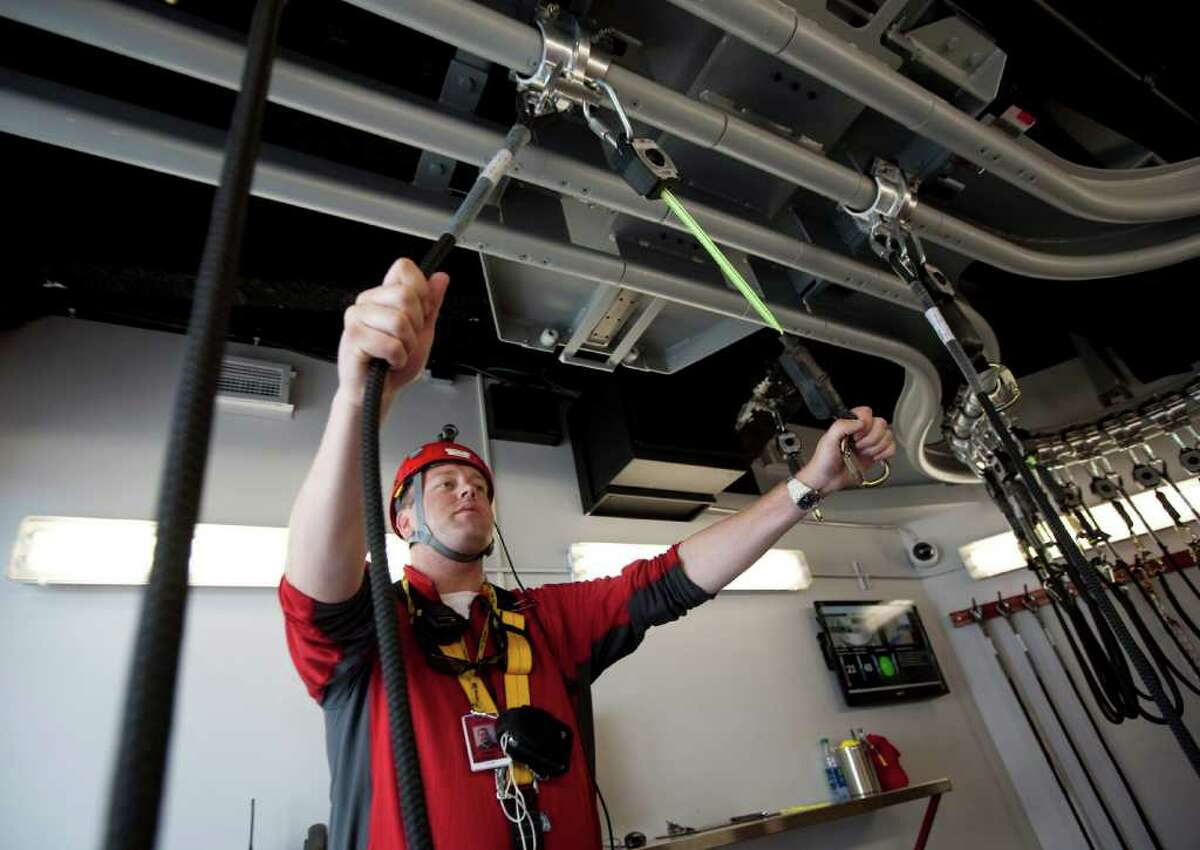 Lead EdgeWalk guide Chris Hall explains the harness and rail system in Toronto Wednesday, July 27, 2011.