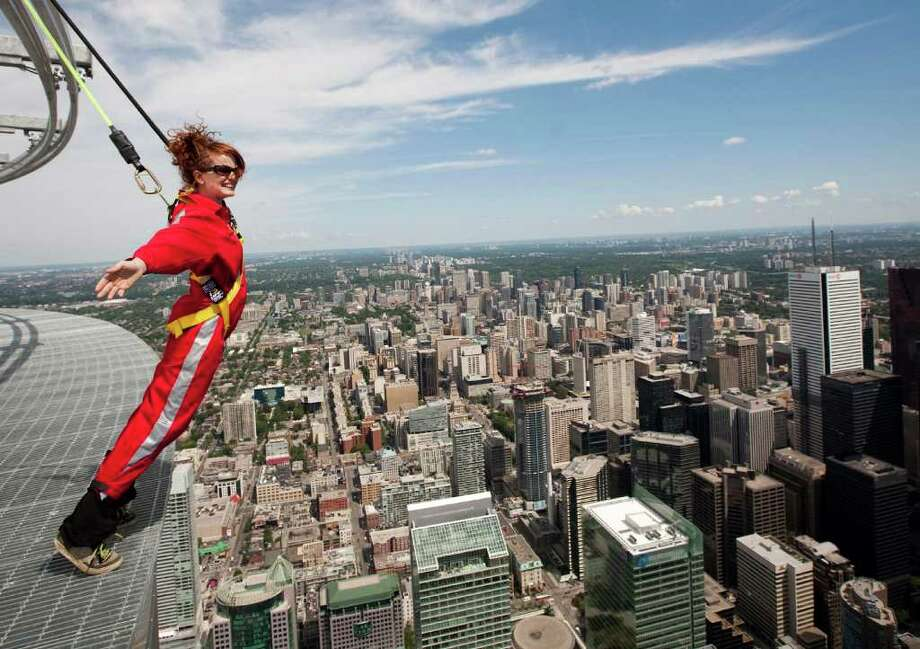 """Toronto's CN Tower just gave reporters a chance to try out its new EdgeWalk, which bills itself as """"the world's highest full circle hands-free walk."""" Participants strap onto an overhead safety rail and then can walk on a  5-foot- wide ledge encircling the top of the Tower's main pod, 1,168  feet (116 stories) above the ground.  Here's Canadian Press reporter Alex Posadzki trying it out on Wednesday, July 27, 2011. Photo: AP"""