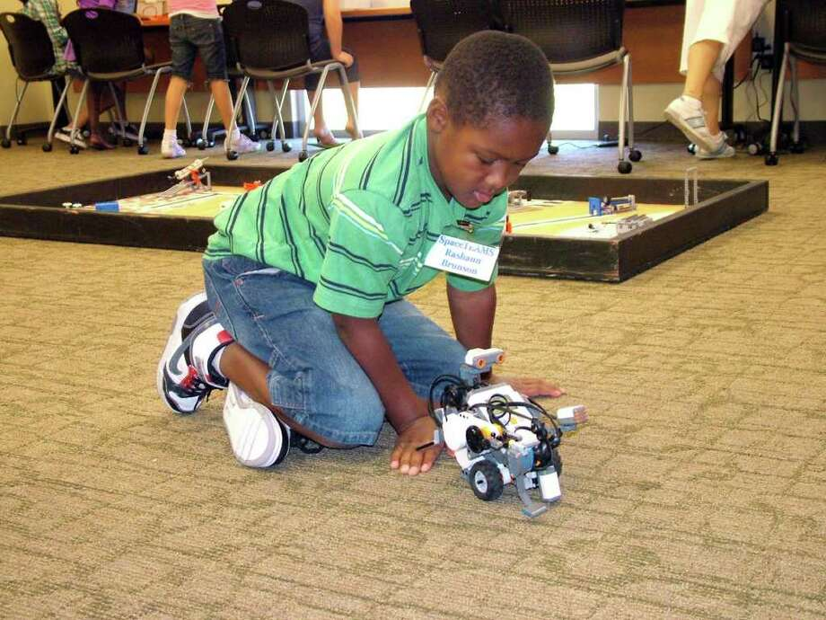 "Rashaun Brunson, 8, an upcoming third-grade student at Salinas Elementary School, tests a ""robot"" Monday during the opening day of Northeast Lakeview College's Robotics Camp. Photo: Photo By Pam Howell"