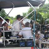 """A film crew is seen on the back of a camera truck after a take during filming of a scene with Ryan Gosling in """"The Place Beyond the Pines."""" The movie was being filmed Thursday on Route 5 in Glenville. (Desiree LaBombard / Special to the Times Union)"""