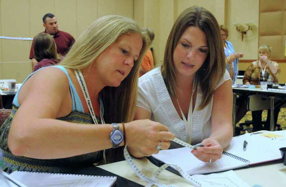 Rachelle Varnon, Houston ISD's St. George Place 4th grade teacher, and 5th grader teacher Melissa O'Donnell, of Austin, measure a string they will use for a pendulum making project during the Houston Mickelson ExxonMobil Teachers Academy at The Woodlands Resort & Conference Center. Over 200 elementary school teachers from  across the country are attending the Academy to hone their skills in math and science teaching. The Academy is designed to equip teachers with innovative tools to teach their students math and science. Photo by David Hopper. Photo: David Hopper, Freelance / freelance