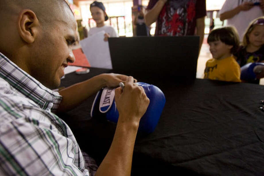 July 15, 2010:Juan Diaz signs a boxing glove for Nathan Salgado, 4, at the Edwards Cinema and IMAX in the Marq*E Entertainment Center in Houston as part of the promotion for his rematch against Marquez. Photo: Johnny Hanson, Chronicle