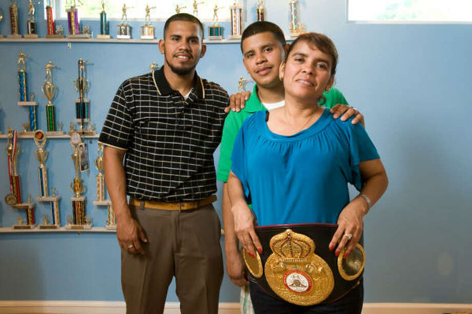 April 22, 2009: Olivia Diaz wears her son Juan's WBA lightweight championship belt. Behind her is her other son, Jose. Photo: Nick De La Torre, Chronicle