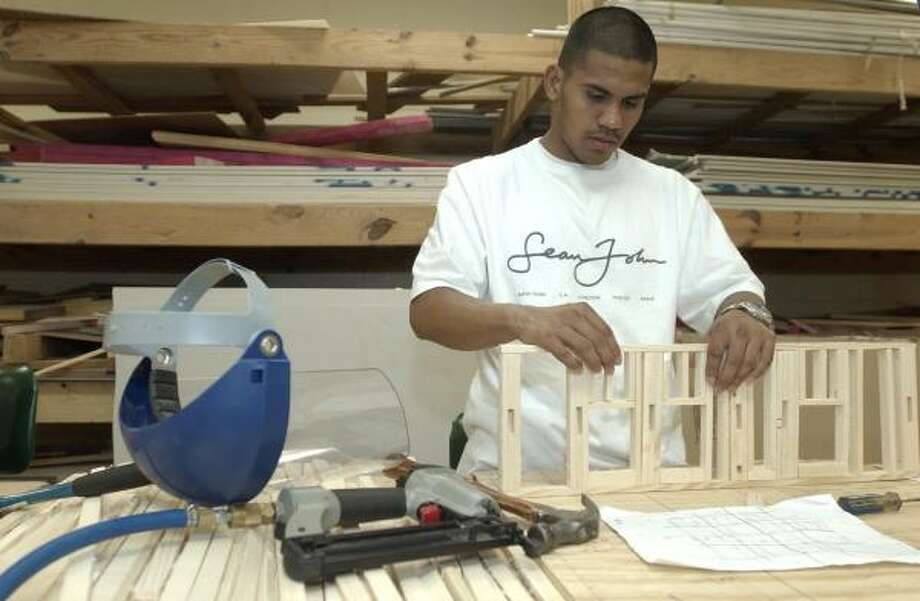 July 13, 2004: Four days before fighting for his first world title, Juan Diaz constructs a scale-model house during a class at Houston Community College. Diaz was also studying pre-law. Photo: Melissa Phillip, Chronicle