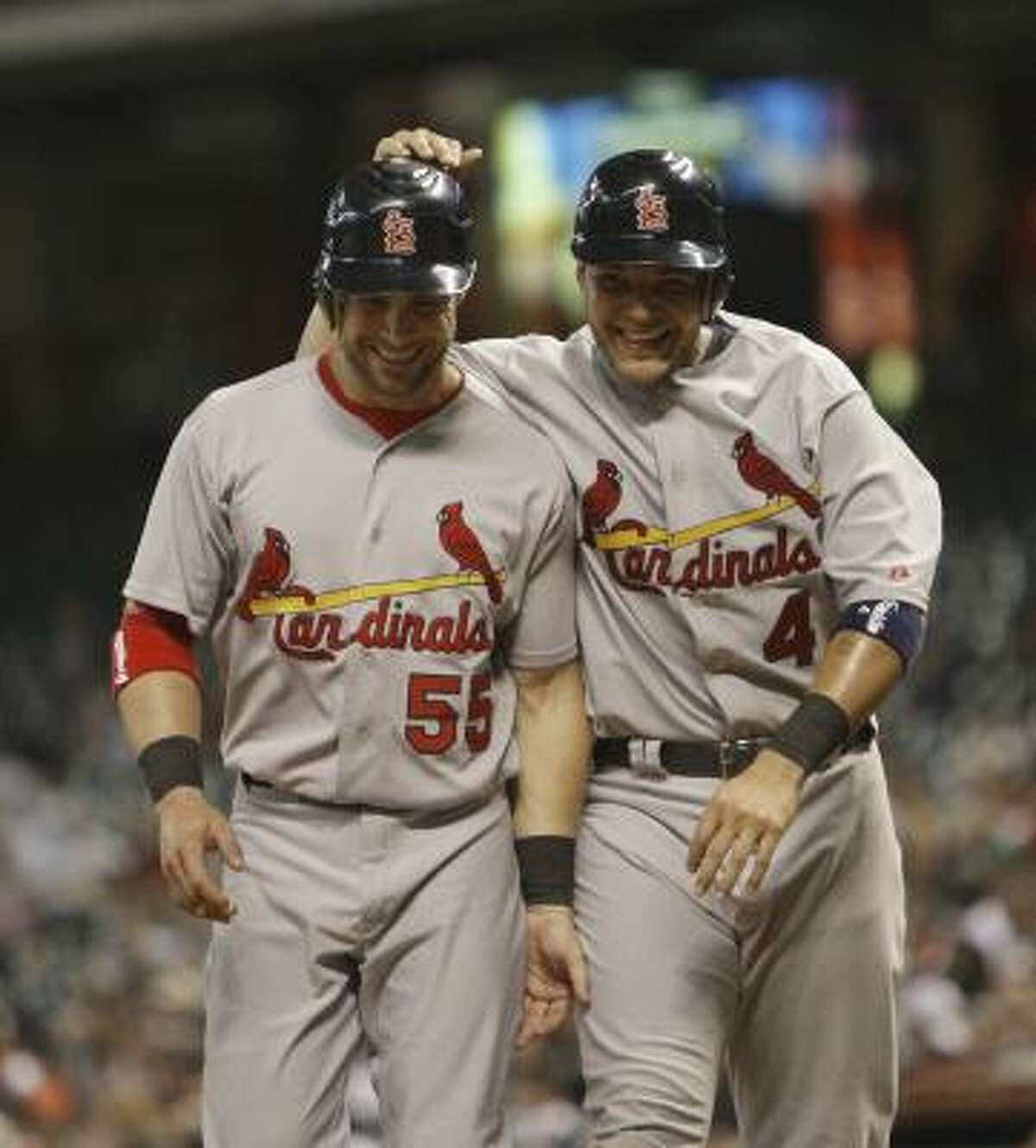 Yadier Molina pats Skip Schumaker on the head after they scored on a double by pitcher Jake Westbrook.
