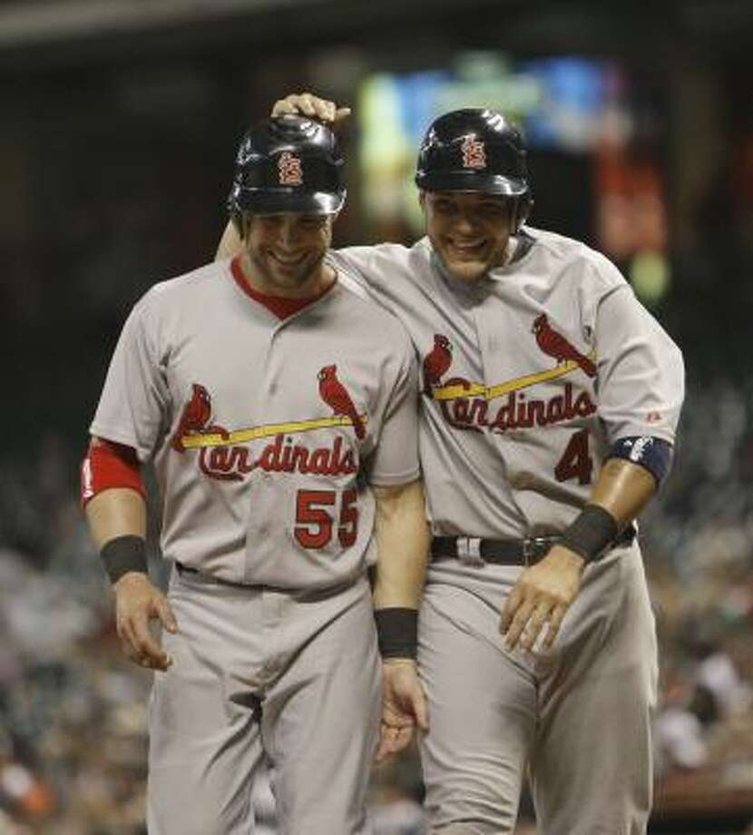 Yadier Molina pats Skip Schumaker on the head after they scored on a double by pitcher Jake Westbrook. Photo: Bob Levey, Getty