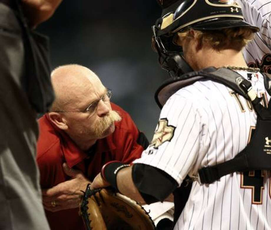 Astros assistant trainer Rex Jones checks on catcher J.R. Towles after he was hit by a ball. Photo: Bob Levey, Getty