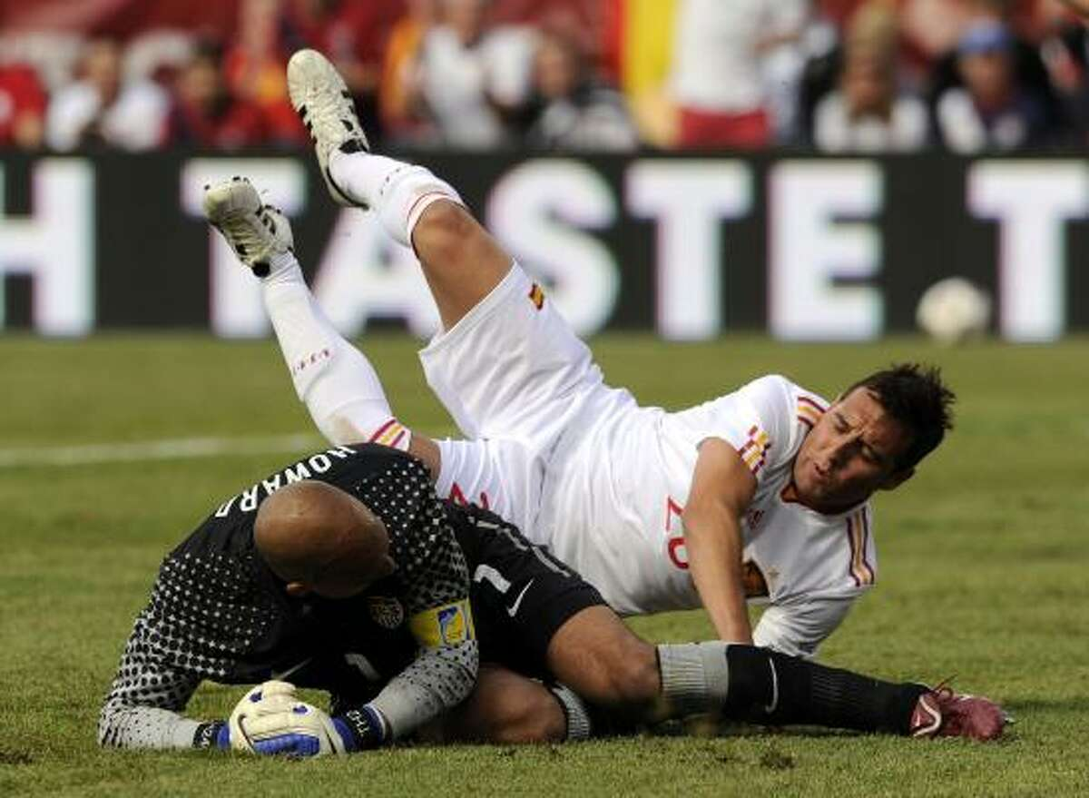 Tim Howard (L) and Santiago Cazorla get tangled up during the U.S and Spain friendly.