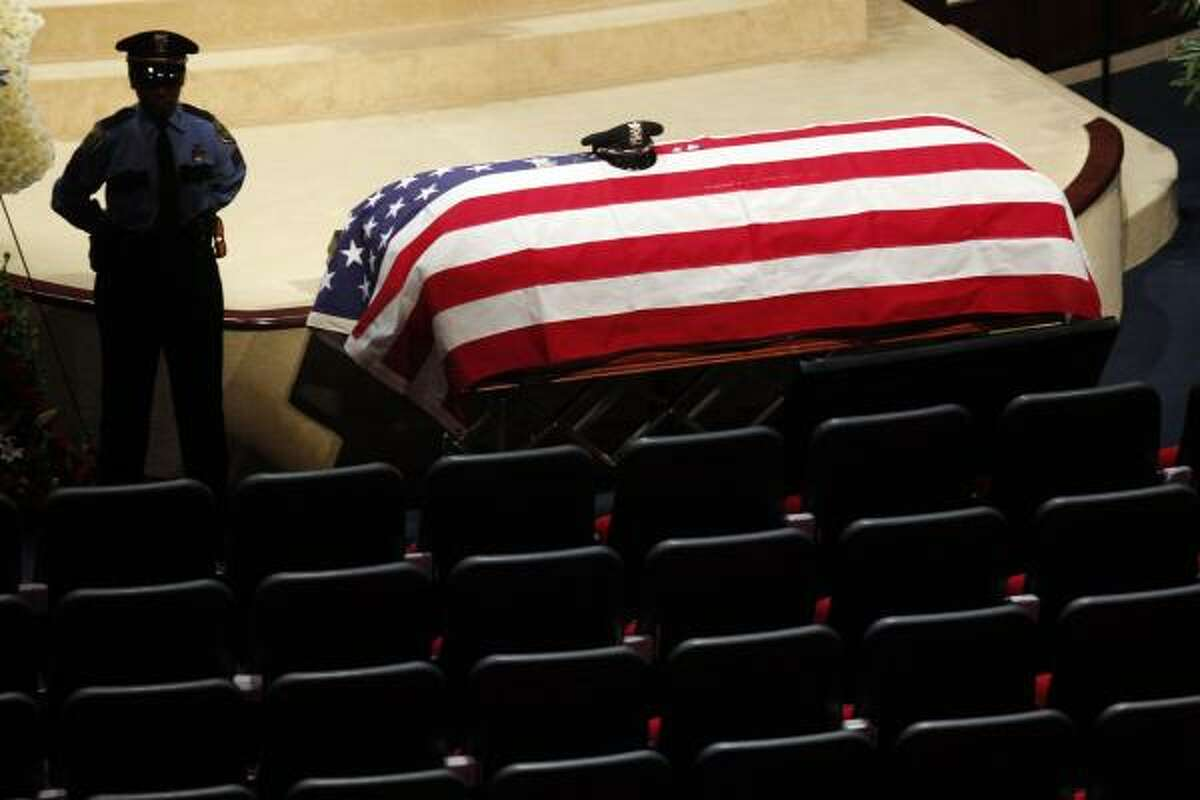 A HPD officer stands near the casket of HPD officer Kevin Will, 38, before his funeral at Champion Forest Baptist Church in Houston. Johoan Rodriguez, 26, is being charged with intoxication manslaughter of a peace officer, felony evading in a motor vehicle and possession of a controlled substance after officer Will was killed early Sunday.