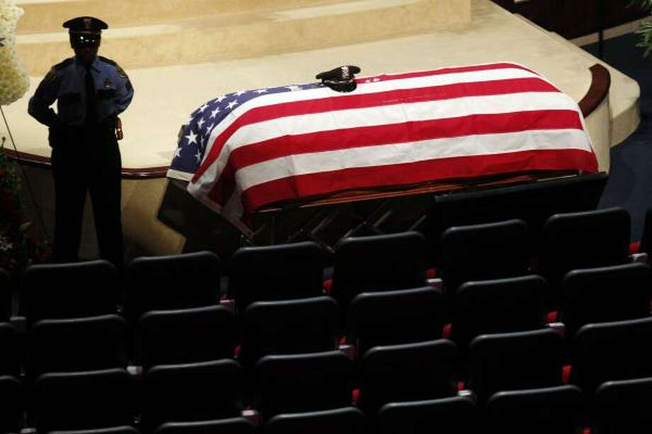 A HPD officer stands near the casket of HPD officer Kevin Will, 38, before his funeral at Champion Forest Baptist Church in Houston. Johoan Rodriguez, 26, is being charged with intoxication manslaughter of a peace officer, felony evading in a motor vehicle and possession of a controlled substance after officer Will was killed early Sunday. Photo: Johnny Hanson, Houston Chronicle