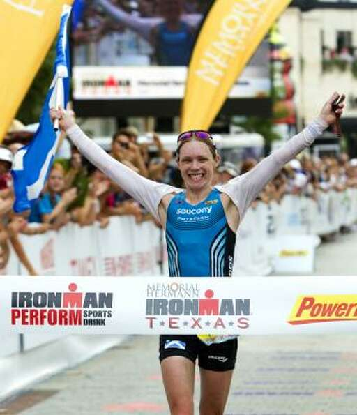 Catriona Morrison, of Scotland, raises her arms as she crosses the finish line to win the women's di