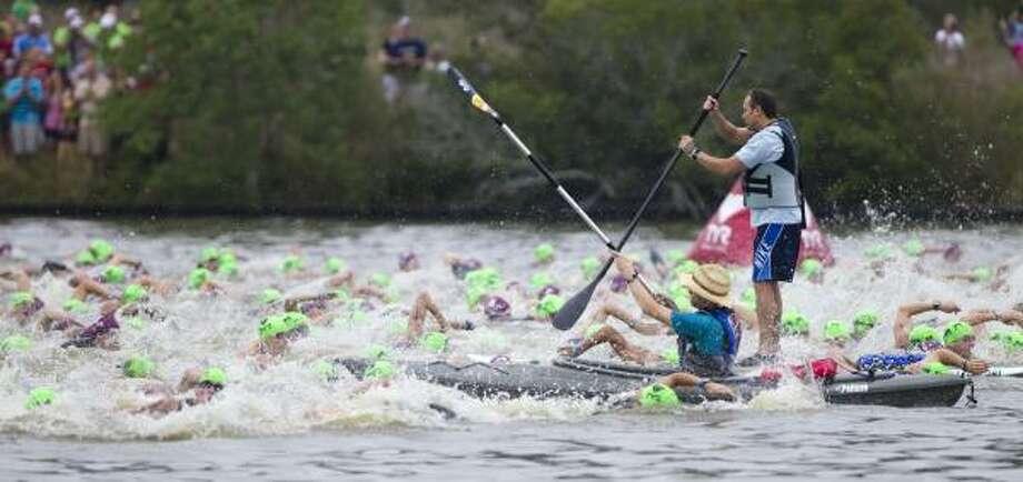Competitors swim past kayakers. Photo: Brett Coomer, Chronicle
