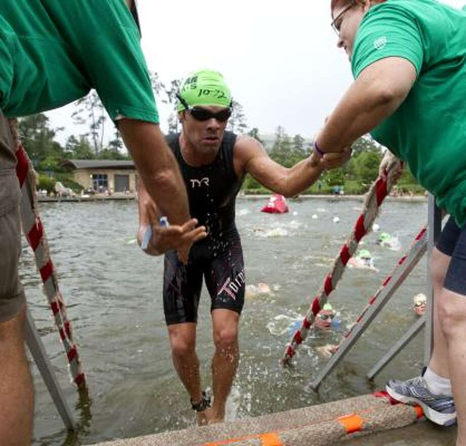 Enrique Ramirez, of Mexico, is helped out of the water by volunteers. Photo: Brett Coomer, Chronicle