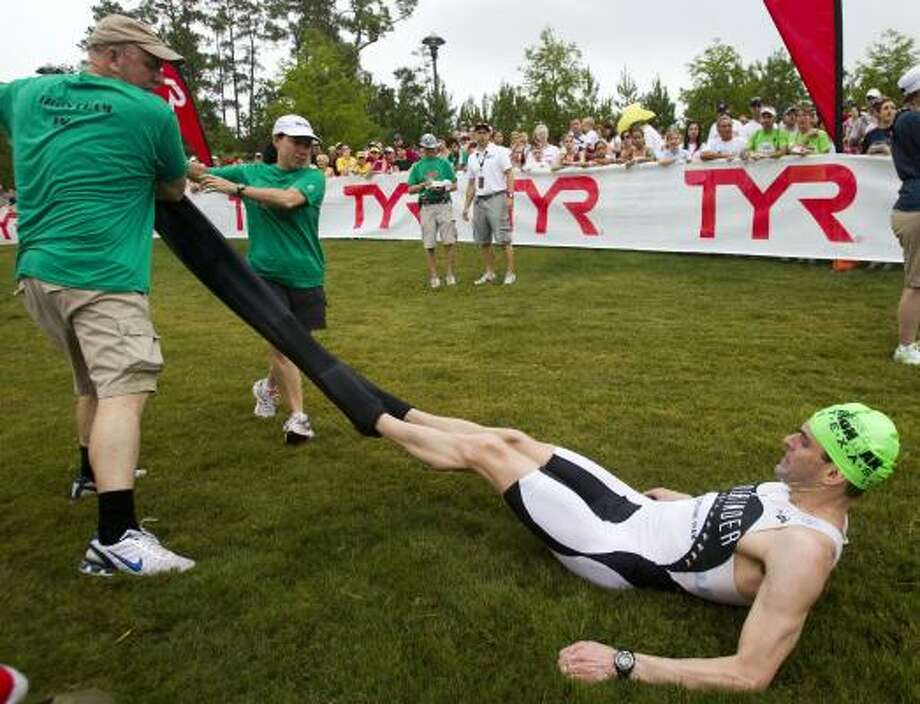 Craig Lanza, of the U.S., is helped out of his wetsuit at the end of the swim portion. Photo: Brett Coomer, Chronicle