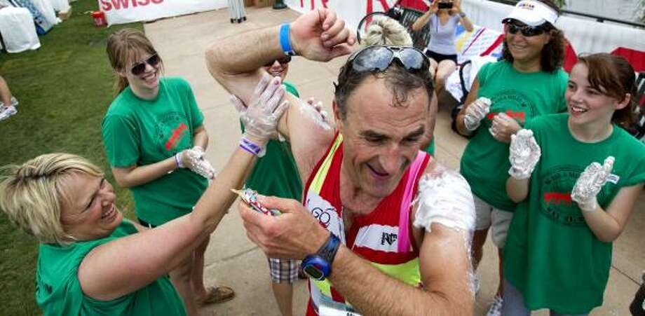 Marc Vedrinelle, of France, has sunscreen applied to his shoulders by volunteers. Photo: Brett Coomer, Chronicle
