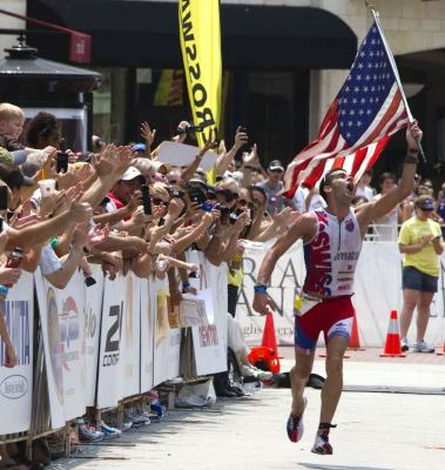 Timothy O'Donnell carries an American flag as he races to the finish line in second place. Photo: Brett Coomer, Chronicle