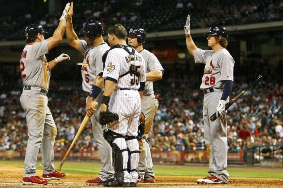 St. Louis' Lance Berkman, left, is congratulated by teammates after hitting a home run to left field, scoring Albert Pujols and Matt Holliday during the top of the sixth inning. Photo: Michael Paulsen, Houston Chronicle