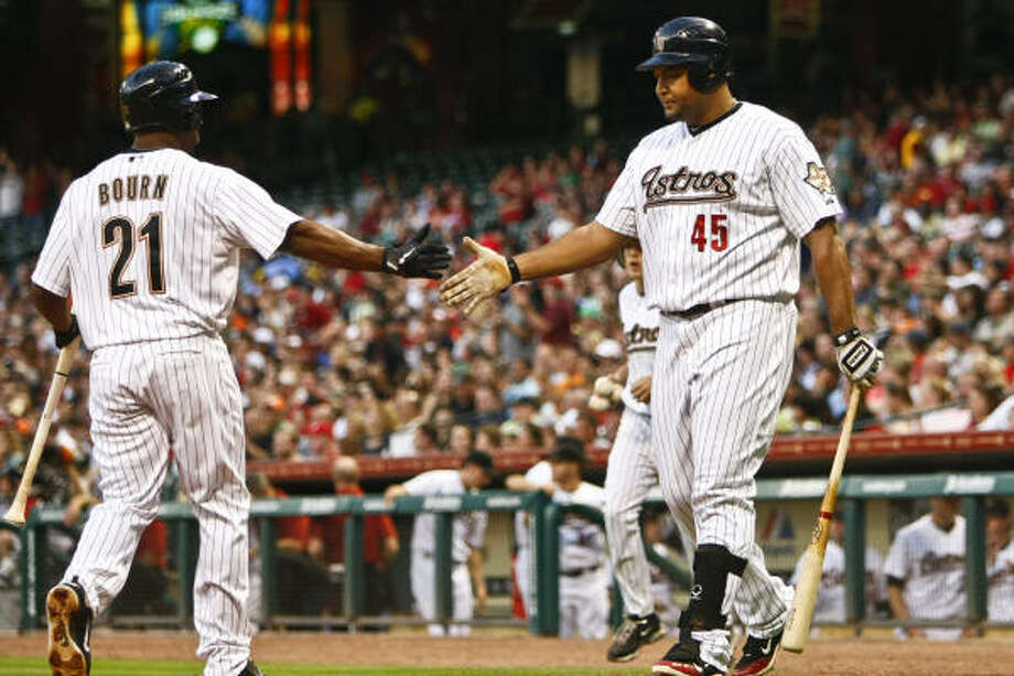 Michael Bourn (21) slaps hands with Carlos Lee after crossing home plate during the third inning. Photo: Michael Paulsen, Chronicle