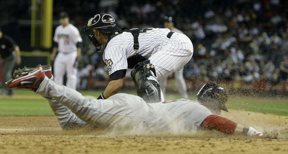 Astros catcher J.R. Towles comes up short on the play as Cardinals Nick Punto slides into home safely in the seventh inning. Photo: Cody Duty, Chronicle