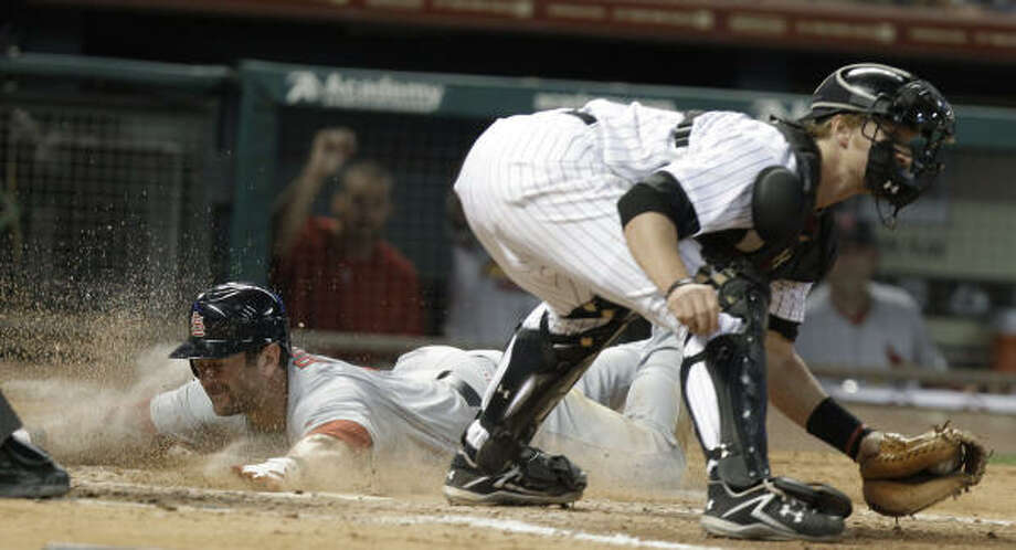 Cardinals' Nick Punto, left, gets a face full of dirt while sliding safely across home plate behind Astros catcher J.R. Towles. Photo: Pat Sullivan, AP